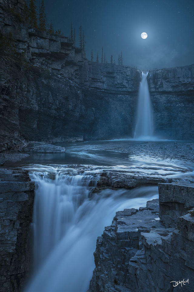 Crescent Falls double waterfall in Alberta, Canada at night with a full moon.