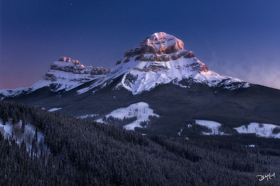 The snowy peak of Crowsnest Mountain in Alberta, Canada receives the first light of sunrise with stars in the sky.