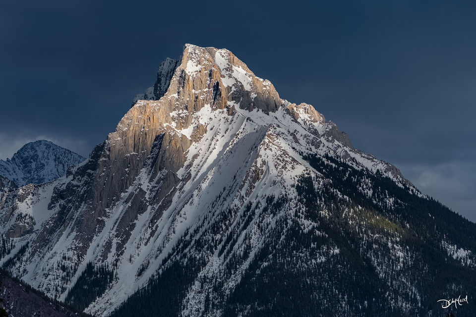 The peak of Gap Mountain in Kananaskis, Alberta, Canada receives late afternoon sunlight with dark clouds in the background.