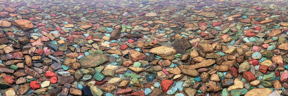 Colorful rocks beneath the clear water of Two Medicine Lake in Glacier National Park, Montana.
