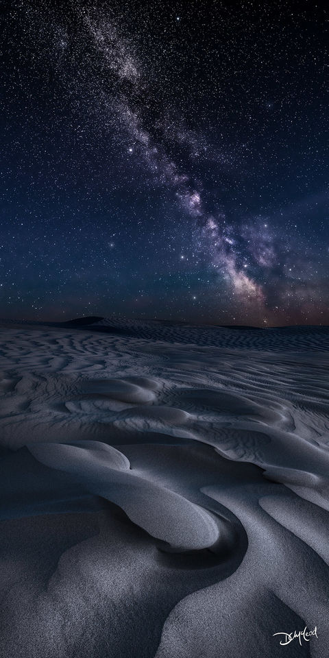 The Milky Way and stars shine in the sky at night over the dunes of The Great Sandhills, Saskatchewan.