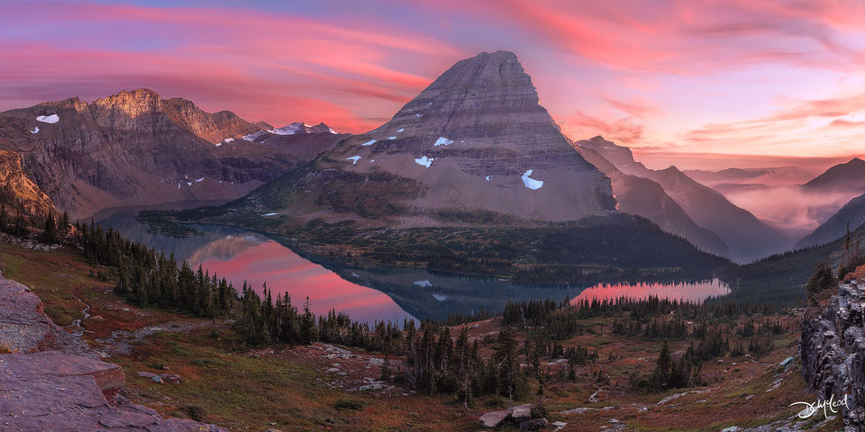 Panorama view of Bearhat Mountain with colorful sunset clouds reflecting in Hidden Lake in Glacier National Park, Montana.