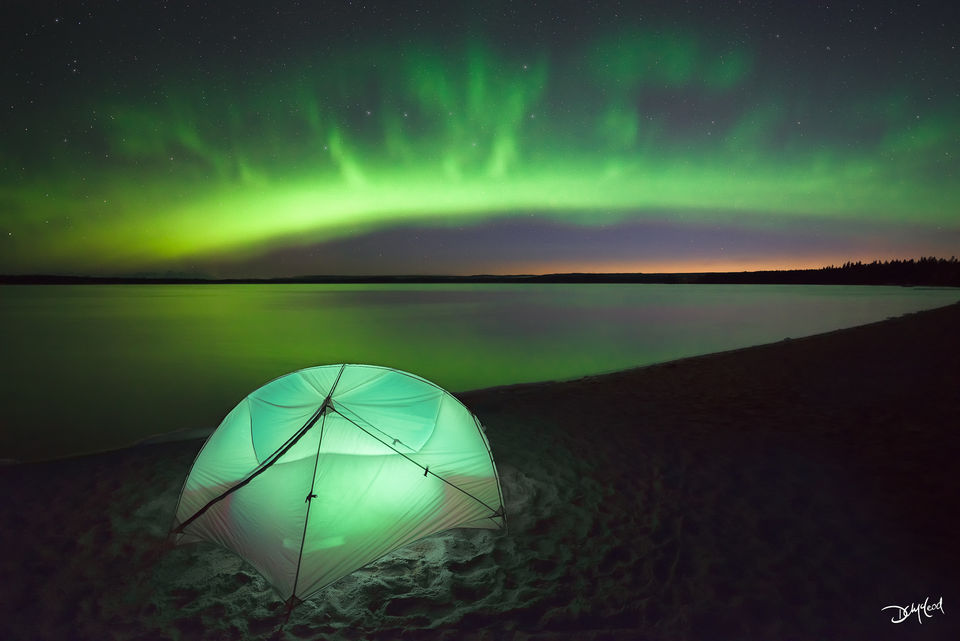 Nighttime view of a small tent on the beach of a lake with the aurora borealis and stars in Saskatchewan, Canada.