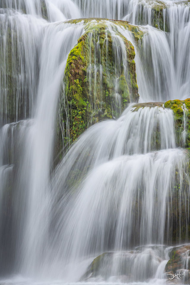 White water cascades over green mossy rocks at Lower Lewis Falls, Washington.