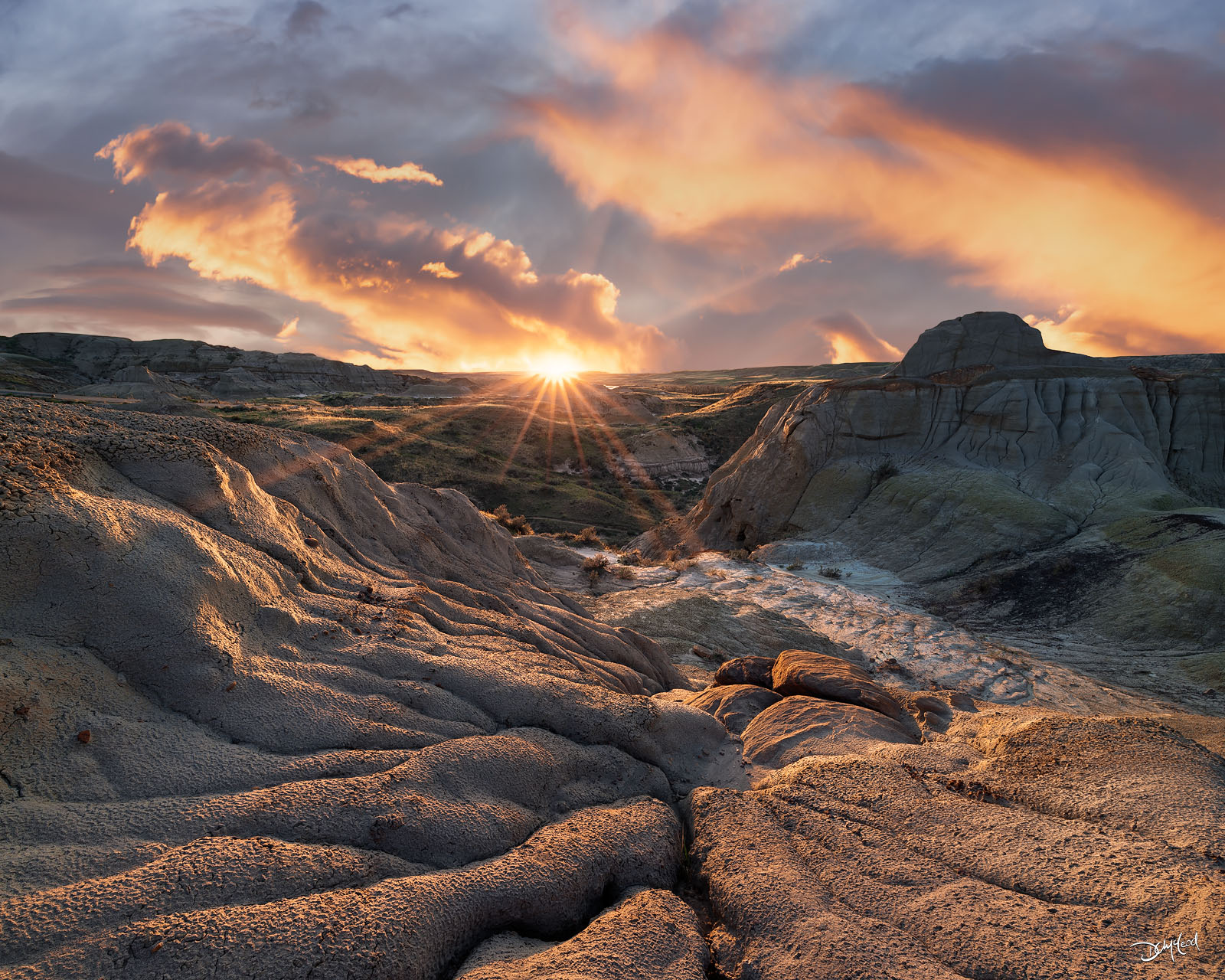 Badlands in Dinosaur Provincial Park are warmly illuminated by  the setting sun on the horizon with a colorful sky.