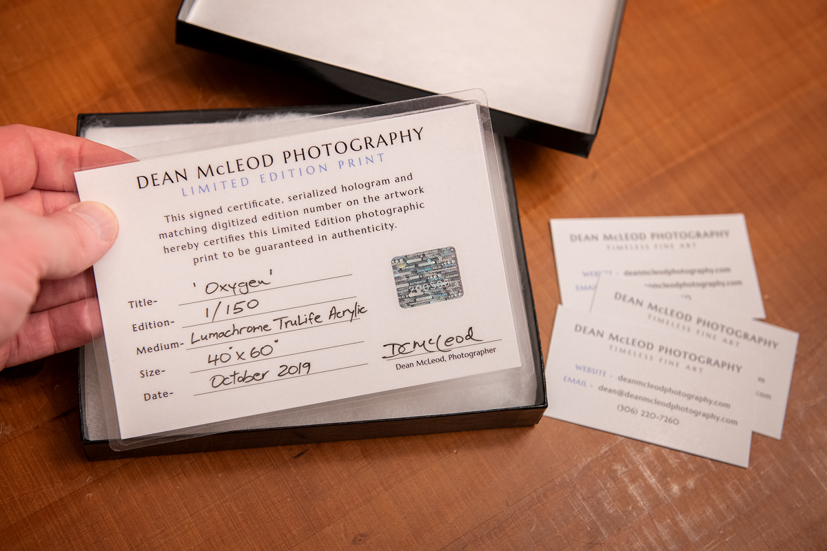 A Dean McLeod Photography certificate of authenticity shown as it is removed from a small black box.