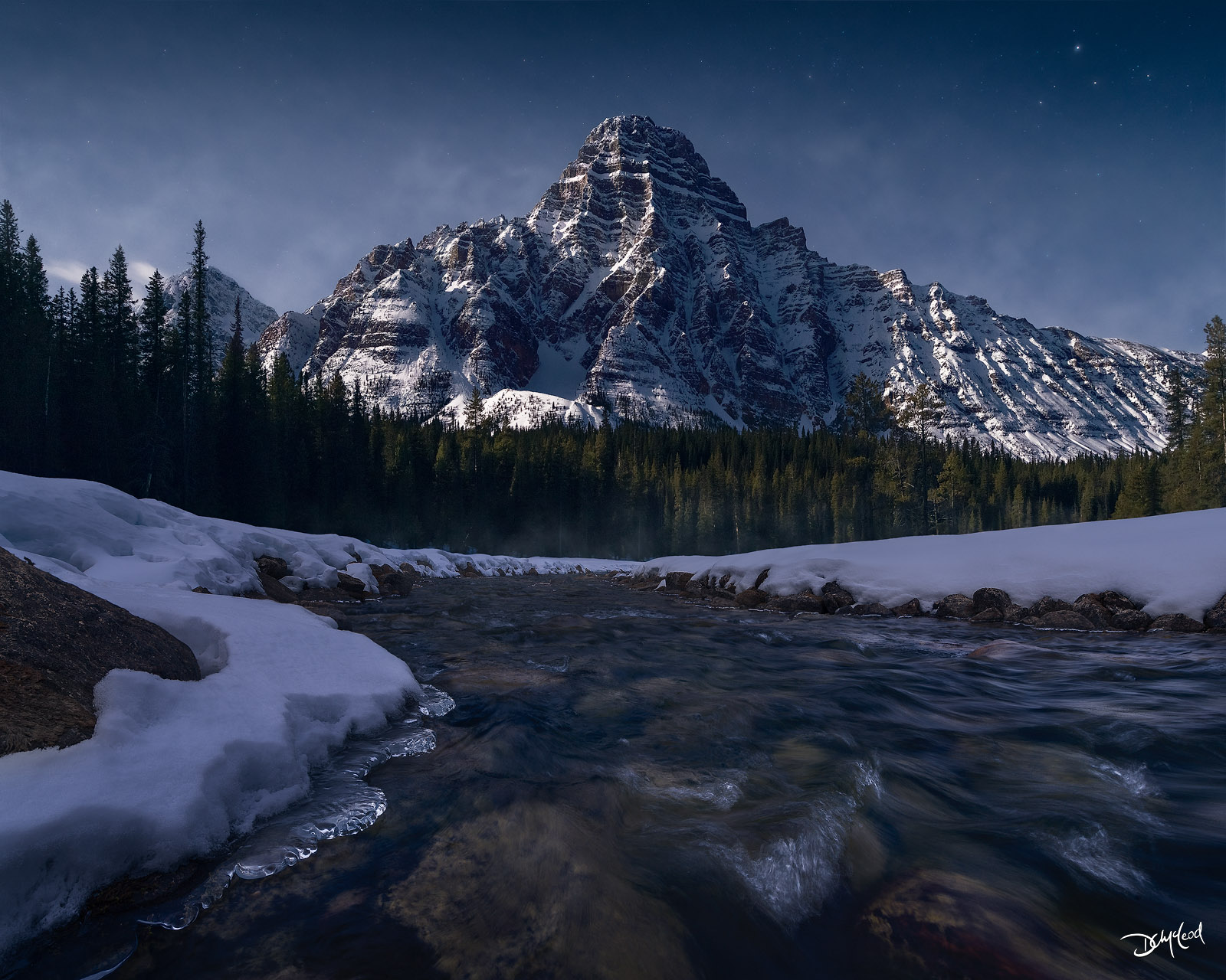 Mount Chephren in Banff National Park receives bright sidelight from the moon during the night with ice and snow on the shore of the river in the foreground.