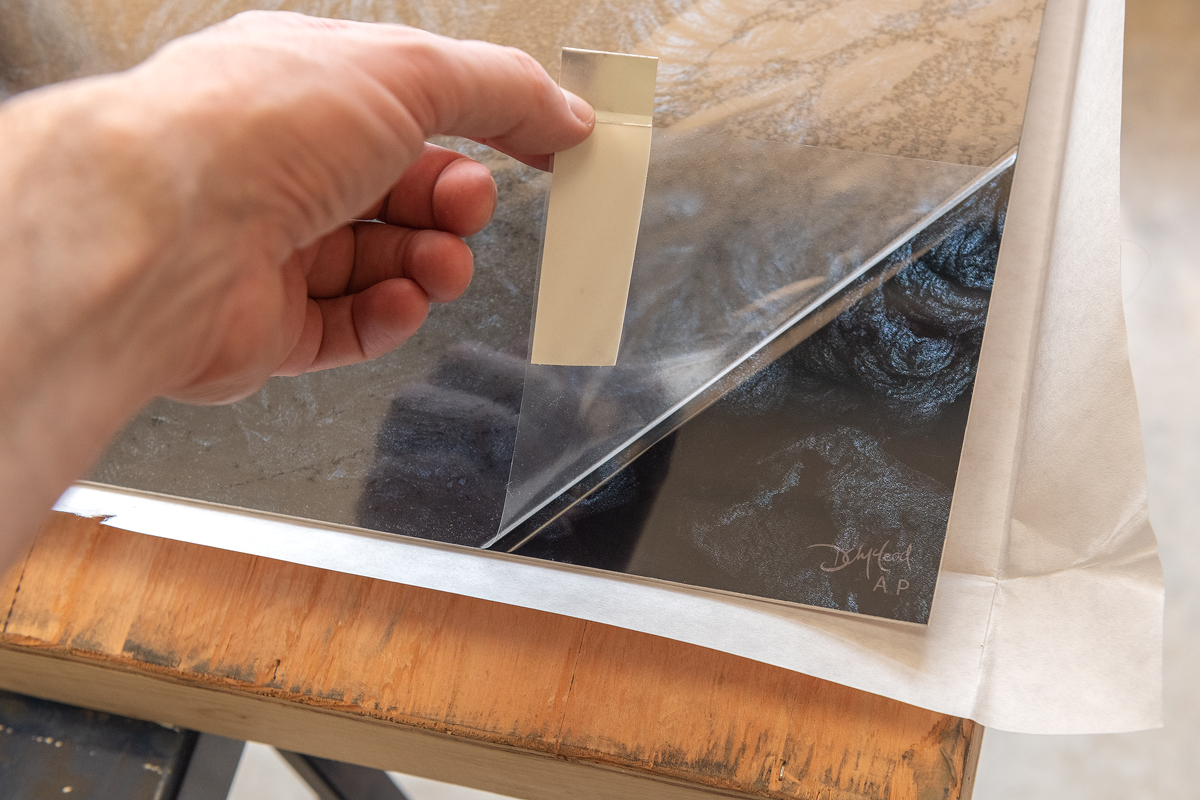 Peeling the protective film off of a new photographic metal print.