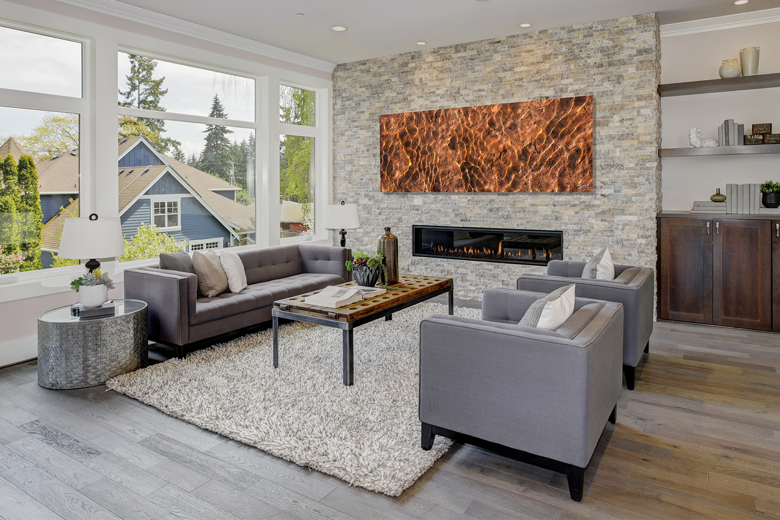 Modern great room with a floor to ceiling stone fireplace. Luxur