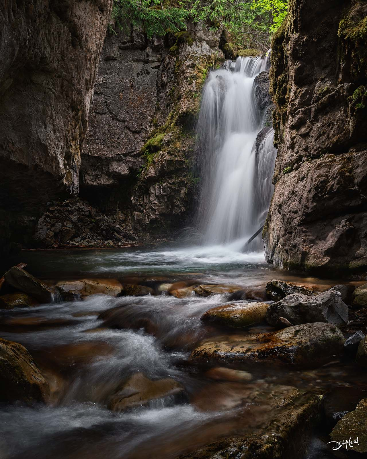 Small waterfall in a dark canyon on Mount Allan, Kananaskis, Alberta, Canada.