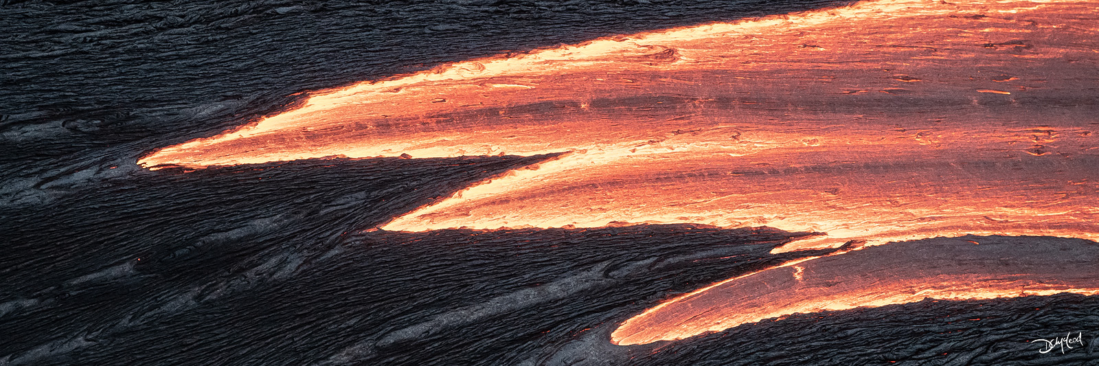 Panorama view of flowing orange lava surrounded by black rock in Hawaii.