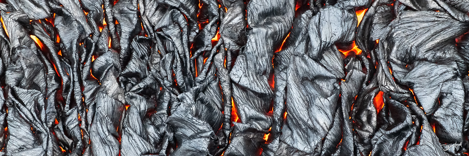 Panoramic view of hot lava beneath a cooling surface crust in Hawaii.
